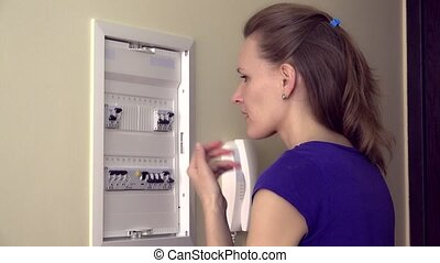 lonely woman pushing lever in fuse box. Static closeup shot.