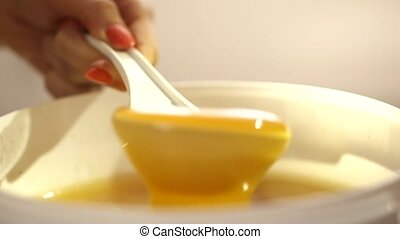 Mixing of golden honey close up clip
