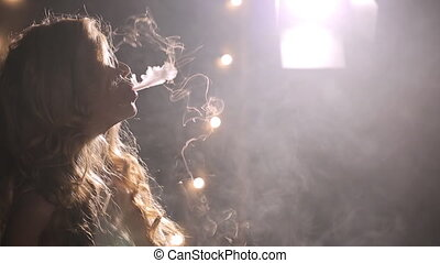 Young woman blows smoking fumes and lamps shine on background