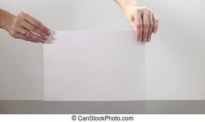 Female hands crumpling a sheet of paper clip