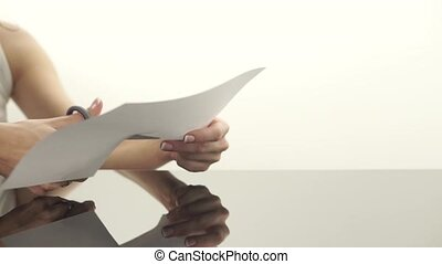 Female hands cutting a sheet of paper with scissors clip