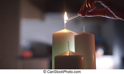 Girl hand lighting up three candles clip