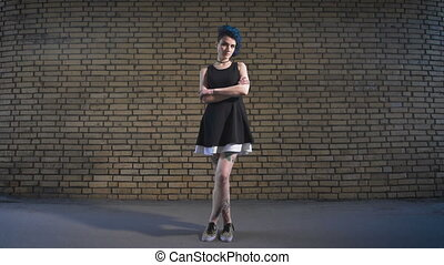Street youth movements and styles. Beautiful girl in a black dress on brick wall background.