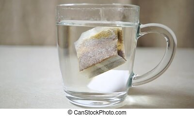 Putting sugar and tea bag in a glass mug with hot water clip