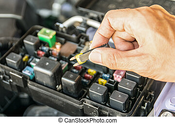 Auto mechanic checking a car fuse