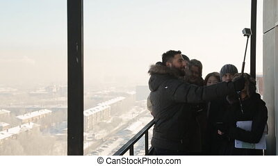 Smiling people make selfie with compact camera from the balcony on the background of a winter city