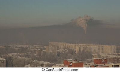 Giant factory chimney emits smoke over the winter city,...