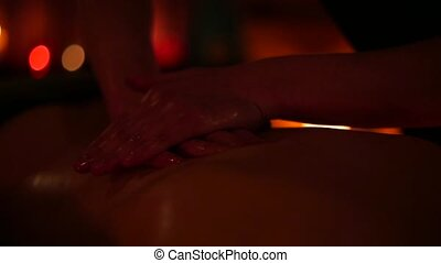 Masseur makes massage with oil for woman