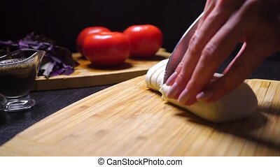 Female hands cutting mozzarella cheese on the wooden cutting...