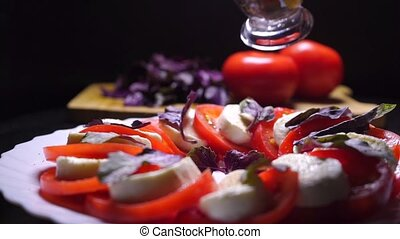 Pouring balsamic sauce on tomatoes and mozzarella cheese...