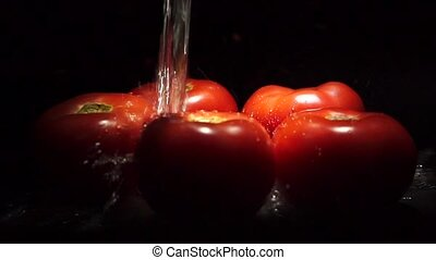 Slow motion of tomatoes and falling water with black...