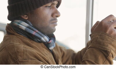 Serious warmly-dressed man-Hindu takes pictures with smart phone through a window in winter