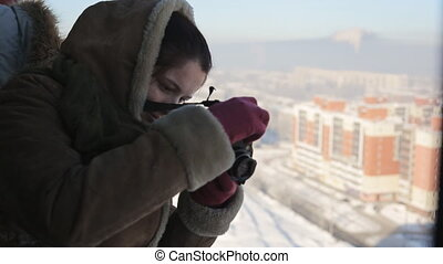 Beautiful woman takes photos of the winter city from a...