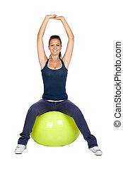 Attractive girl practicing pilates on a big green ball
