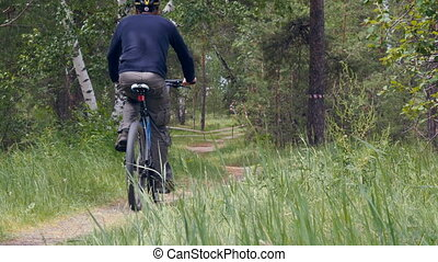 male cyclist riding on a footpath in woods