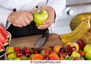 Chef with fruits - Chef cutting a sour apple green