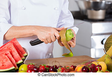 Chef with fruits - Chef cutting a delicious kiwi acid
