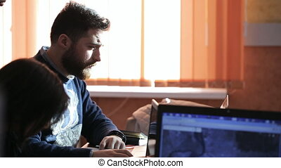 Bearded man looks at the laptop screen and asks other people about something