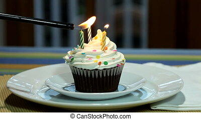 Happy Birthday Cupcake With Candles Being Lit and Burning...