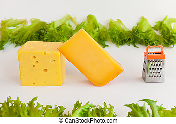 Pieces of cheeses, metal grate for preparing  grated cheese and leaves of frillis