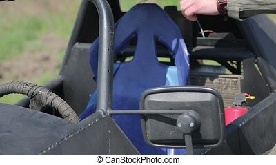 Man in helmet sits in the buggy