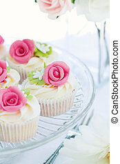 Rose cupcakes served on a glass cakestand