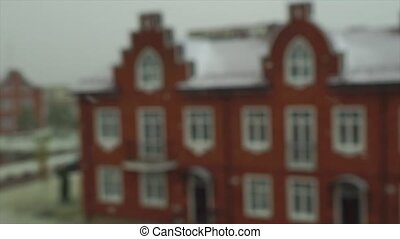 Slow motion video of snowflakes in front on red brick town...