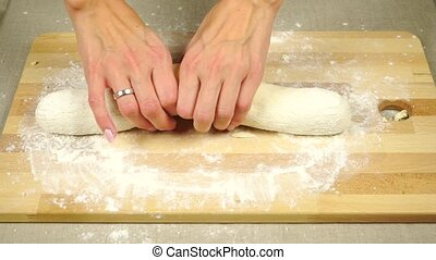 Woman hands rolling out dough on a wooden board clip