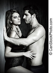 love by the wall - Black-and-white portrait of a sexy couple...