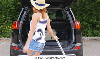 Beautiful girl in a car trunk loads auto trip