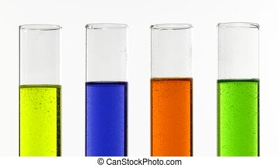 colored liquids abuzz - Closeup of colored test tubes on...