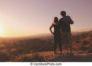 couple watching sunset from the mountain