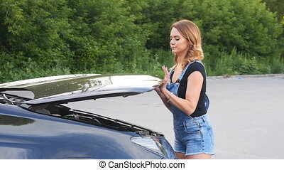 young girl with a broken car with open hood - young brunette...