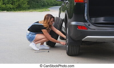 Pretty girl replacing tyres