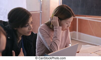 Two women actively discuss tasks on lesson using laptop....
