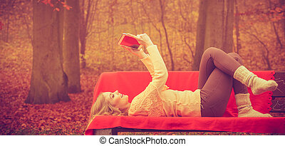 Girl sitting on bench with tablet - Modern education...