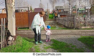 Little girl is walking with her grandmother on the village...