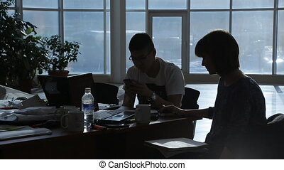 Pair of entrepreneurs sits at table in dark office in evening