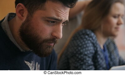 Man with beard attentively works on project in office His...