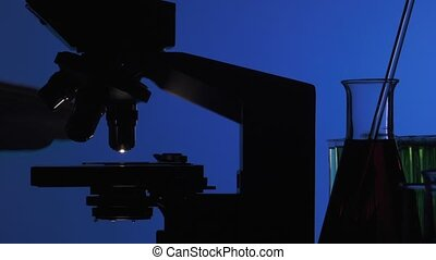 Man manipulating a microscope - shot against the light on...