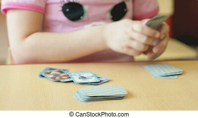 A little girl plays the playing cards at the table