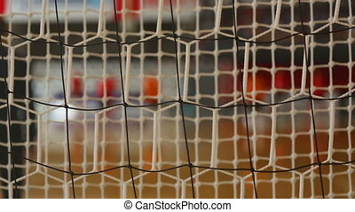 Futsal background with goalie net and players out of focus