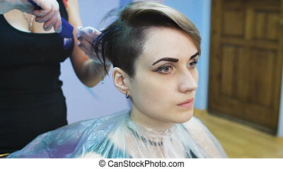 Stylist in a beauty studio does hair dye She decided to...