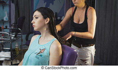 Pretty young girl in a beauty salon for hair gets health...