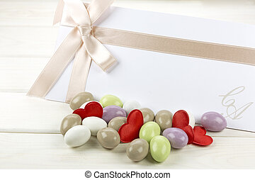 Colored sugared almonds and wedding paper
