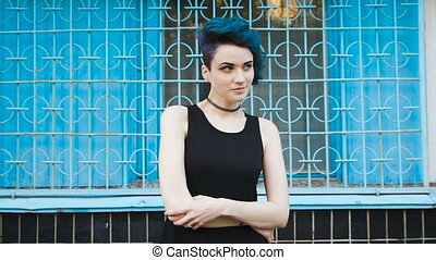 Street punk or hipster girl with blue dyed hair. It is in a...