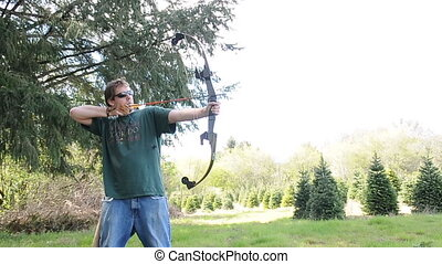 Man Casually Practicing Archery wit - Young white Caucasian...