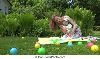 mother with small baby play with colourful ball in green...