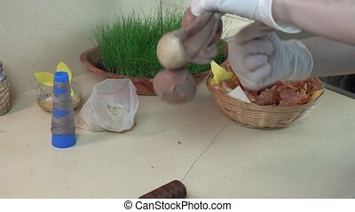 hands put onion shells, rice and egg into sock and string....