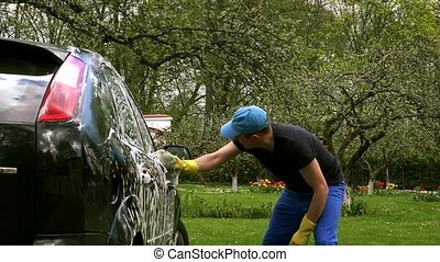 Male worker washing car on open air - Male worker with soapy...